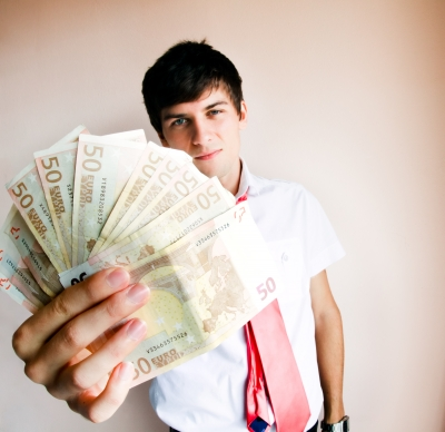 Man holding fan of fifty dollar bills